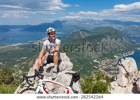 Cyclist on the top of a hill sitting on a background of the bay and the sea