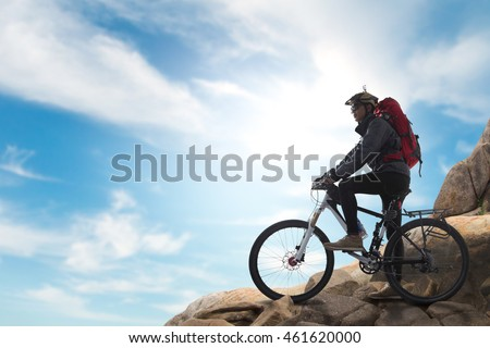 Cyclist on the top of a hill with blue sky clouds