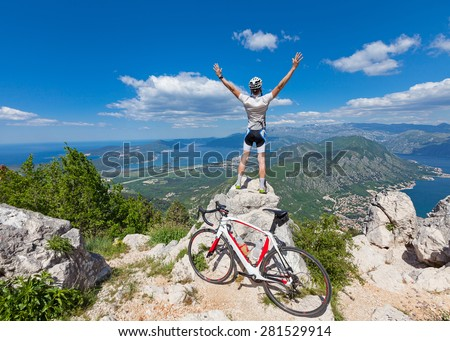 Cyclist on the top of a hill with their hands up - stock photo