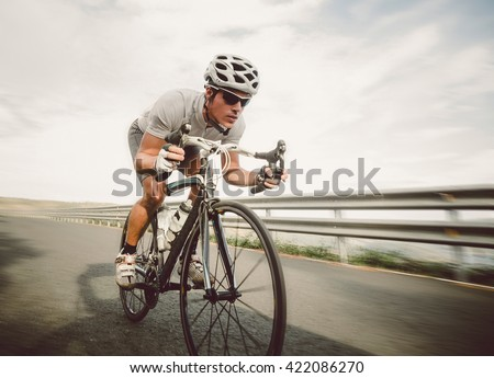 Cyclist pedaling on a racing bike outdoors in a sunny day