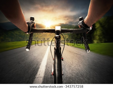 Cyclist pedaling on a street in daylight - stock photo