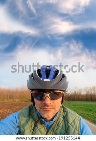 cyclist portrait against a deep blue sky on a sunny day - stock photo