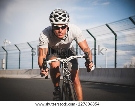 Cyclist portrait in action on the road in a sunny day. - stock photo