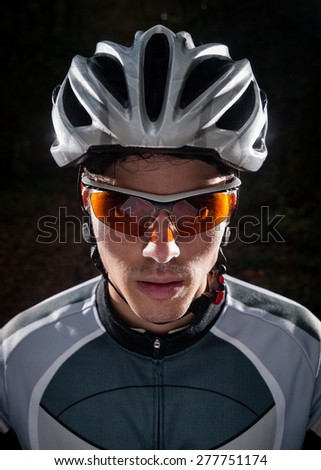 Cyclist portrait with flash light in a forest outdoors - stock photo