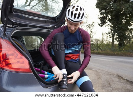 Cyclist prepares for a ride sitting in the back of his car - stock photo