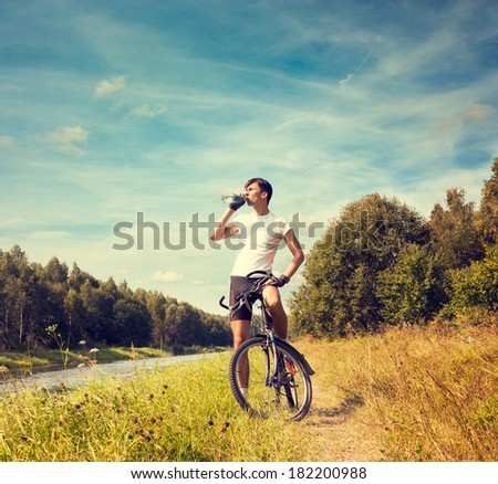 Cyclist Resting and Drinking Water at Summer River Background. Healthy Lifestyle Concept. Copy Space. - stock photo