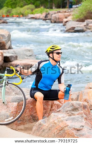 Cyclist rests in a city park by the river - stock photo