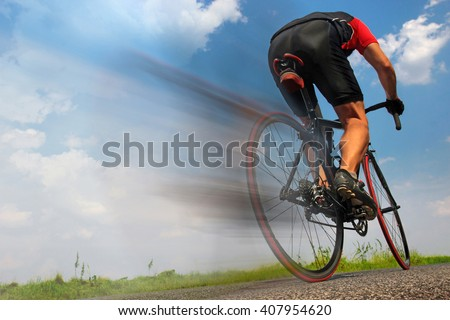 Cyclist ride on road with blurry movement behind the back wheel. Cyclist riding fast on the asphalt road. Back of road racing cyclist. Speeding cyclist on the road. Blurred motion of cyclist on road. - stock photo