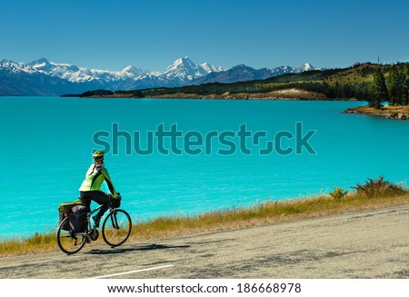 cyclist rides along the winding asphalt mountain road along Lake Pukaki view from Glentanner Park Centre near Mount Cook, on a background of blue sky with clouds, snowy Southern Alps.  - stock photo