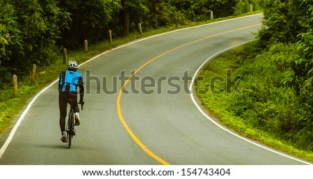 Cyclist riding a bike on an open road. - stock photo