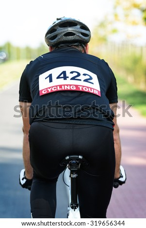 Cyclist riding a bike with race number on his back - stock photo