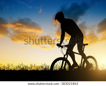 Cyclist riding a mountain bike at sunset