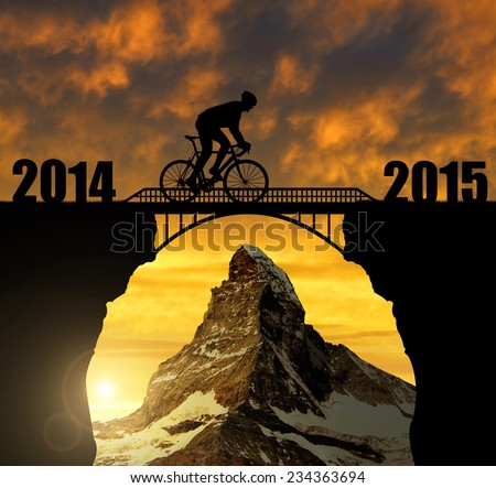 Cyclist riding across the bridge at sunset. In the background Matterhorn. Forward to the New Year 2015  - stock photo