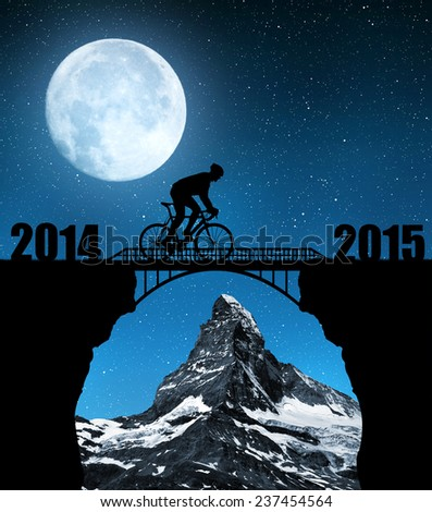 Cyclist riding across the bridge in night. In the background Matterhorn. Forward to the New Year 2015 - stock photo