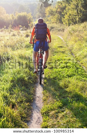 Cyclist riding away into the distance on the road illuminated by the rays sun . Back to us