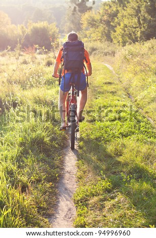 Cyclist riding away into the distance on the road illuminated by the rays sun . Back to us - stock photo