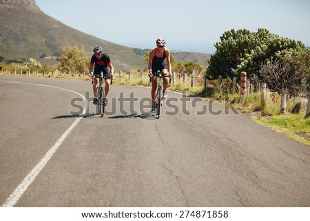 Cyclist riding bikes on open road. Triathletes cycling on bicycles. Practicing for triathlon race. - stock photo