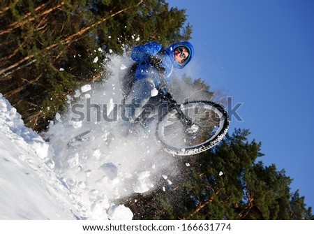Cyclist riding on a mountain bike in the snow in the winter forest - stock photo