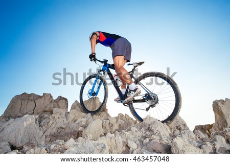 Cyclist Riding the Bike Down Hill on the Mountain Rock
