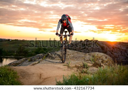 Cyclist Riding the Bike Down Hill on the Mountain Rocky Trail at Sunset. Extreme Sports - stock photo