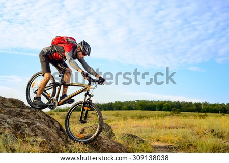 Cyclist Riding the Bike Down Rocky Hill. Extreme Sport Concept. - stock photo