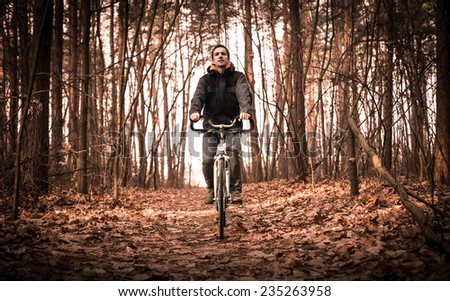 Cyclist riding the bike in the autumn forest - stock photo