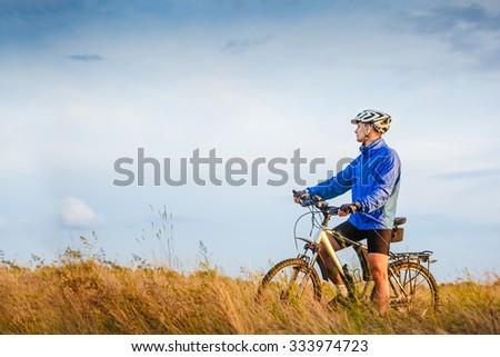 Cyclist Riding the Bike on the Beautiful Meadow Trail