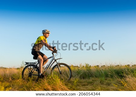 Cyclist Riding the Bike on the Beautiful Spring Meadow