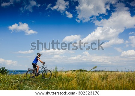 Cyclist Riding the Bike on the Beautiful Spring Meadow Trail  - stock photo