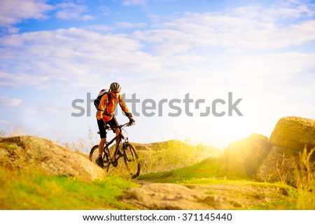 Cyclist Riding the Bike on the Morning Mountain Trail - stock photo