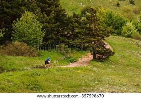 Cyclist riding uphill, training, mountains, Crimea - stock photo
