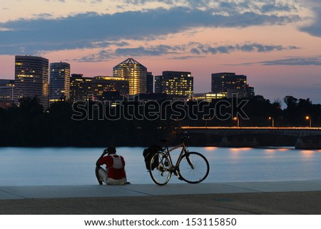 Cyclist silhouette and Rosslyn skyscrapers at sunset in Washington DC - United States - stock photo