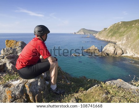 Cyclist sitting, staring at a coastal landscape on a sunny day and after sports. the picture was taken in Ferrol, Galicia, Spain. - stock photo