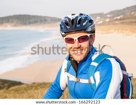 Cyclist smiling and looking at camera outdoors in the galician coast.