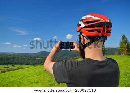 Cyclist taking pictures with smart phone. Caucasian man in bike helmet taking smartphone photo of mountains. Outdoor activity. Copyspace. - stock photo