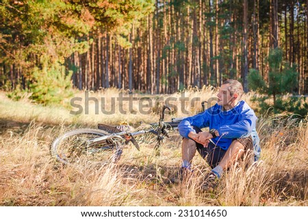 Cyclist with bike have a rest in autumn forest - stock photo