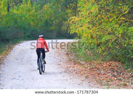 Cyclist woman departing on winding road during fall