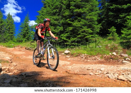 Cyclist woman mountain biking on a rocky road during summer