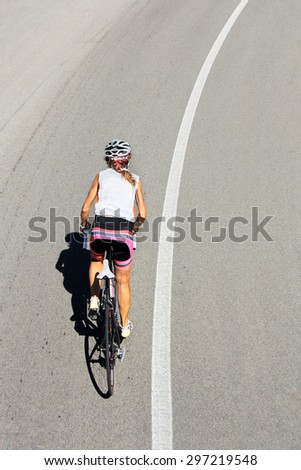 Cyclist woman riding a bike on an open road - stock photo