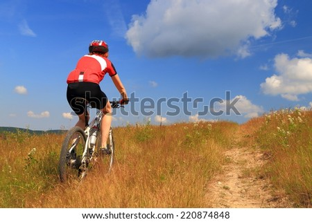 Cyclist woman riding the bike on grass covered trail