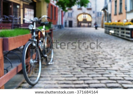 Cyclists at the outdoor cafe with flowers and green grass in the old city of Riga on the street with cobblestones in the summer day. Blurry - stock photo