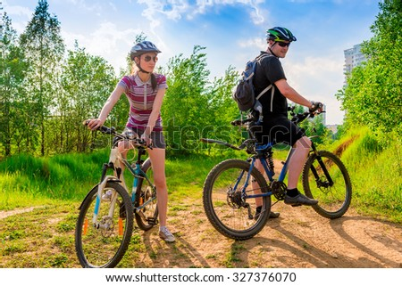 cyclists in helmets and sunglasses resting on a hill - stock photo