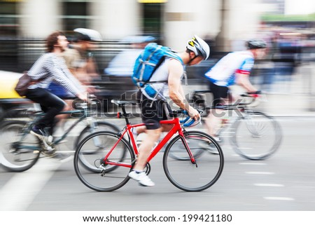 cyclists in motion blur riding in the city - stock photo