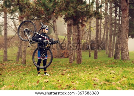 Cyclists preparing for off road training, holding bike on his shoulder. Bad weather. - stock photo