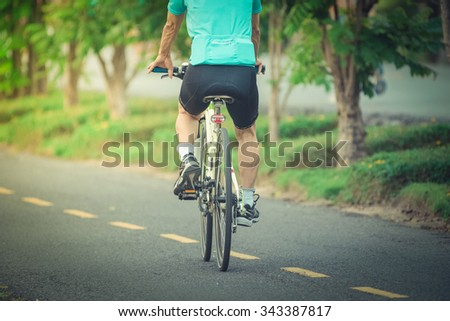 Cyclists ride along bike path in park , vintage