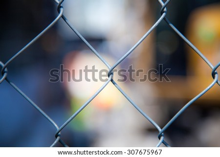 cyclone fence in front of blurred out cityscape