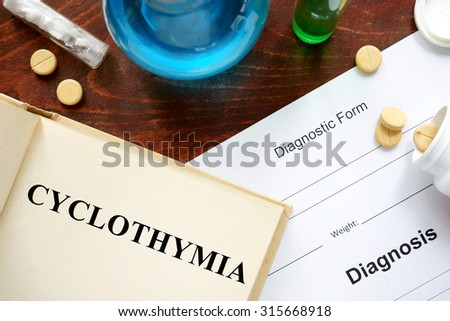 cyclothymia  written on book with tablets. Medicine concept.