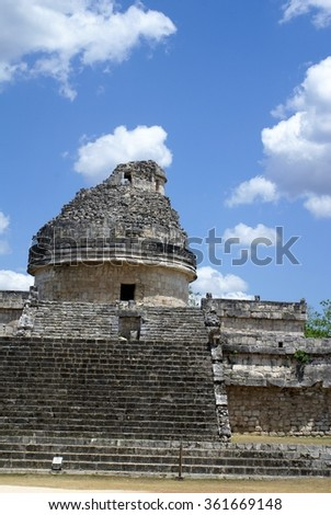 Cylindrical structure in El Caracol Observatory Temple in Chichen Itza, against a blue sky with clouds