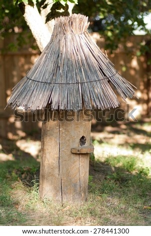 cylindrical wooden beehive with thatched roof in old style - stock photo