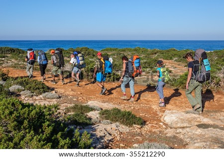 Cyprus. Akamas. Mediterranean Sea. November 24, 2015. A group of tourists with large backpacks are on the sandy road to the sea - stock photo
